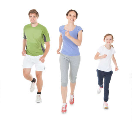Full length portrait of family in sportswear jogging against white background 版權商用圖片