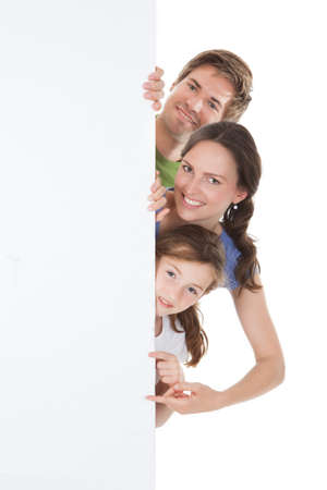 Portrait of happy family peeking from blank billboard over white background