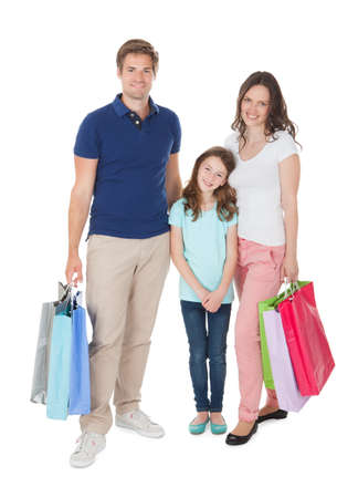Full length portrait of smiling family with shopping bags standing over white background photo
