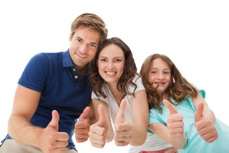 Portrait of happy family gesturing thumbs up together over white background photo