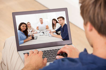 Cropped image of man attending conference meeting on laptop at home photo