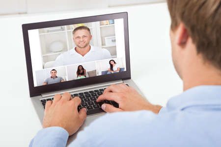 Rear view of businessman video conferencing on computer at desk in office