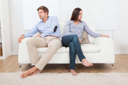 pareja discutiendo: Longitud total de par ignorarse mutuamente mientras está sentado en el sofá en casa