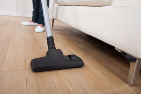 Low section of woman vacuuming hardwood floor at home photo