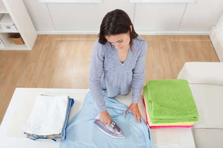 High angle view of woman ironing clothes in house photo