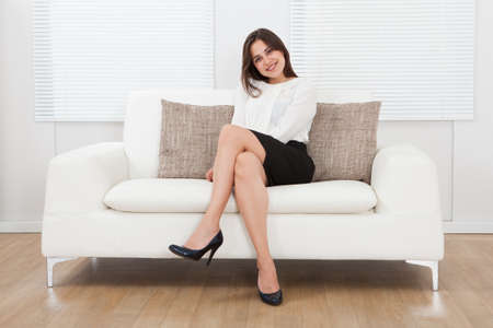 Full length portrait of beautiful young businesswoman sitting on sofa at home