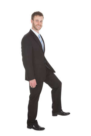 Full length side view of young businessman walking over white background photo