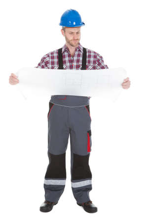 Full length young male worker reading blueprint over white background photo