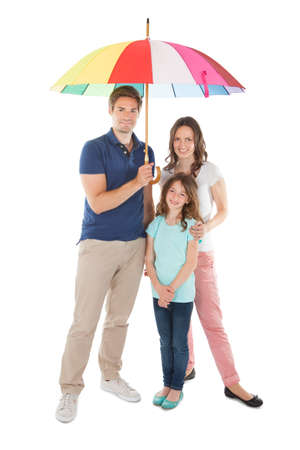 Full length portrait of family standing together below umbrella against white background photo