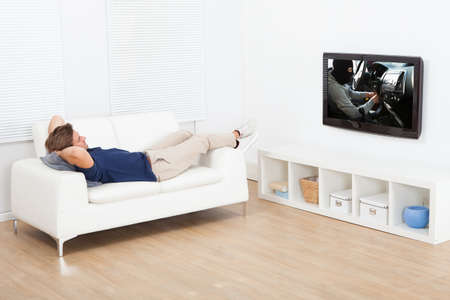 hands behind head: Full length of man watching TV while lying on sofa at home Stock Photo