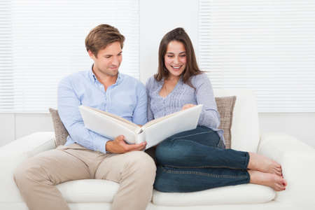 photo album: Happy couple looking at their photo album on sofa at home