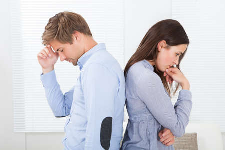 divorcio: Vista lateral de una pareja molesto pie espalda con espalda en el hogar