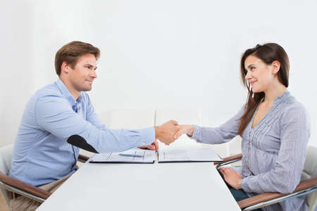 Smiling female candidate shaking hands with businessman in office photo