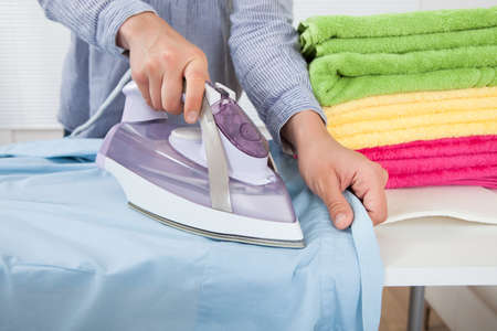 Midsection of woman ironing shirt at home photo
