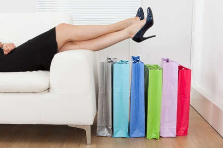 Low section of businesswoman with legs over multicolored shopping bags at home photo