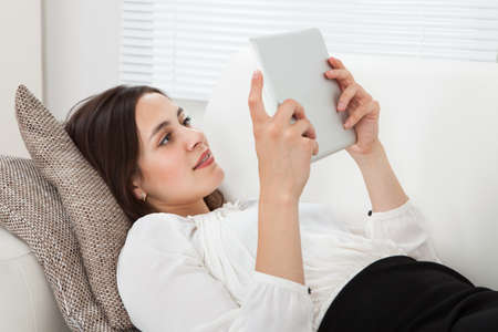 Full length side view of young businesswoman using digital tablet while lying on sofa at home photo