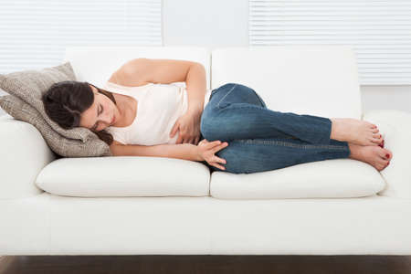 High angle view of young woman suffering from stomachache on sofa at home