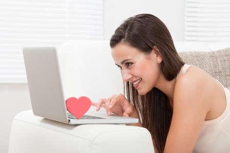 relationship: Vista lateral de uma jovem bonita namoro on-line no laptop em casa