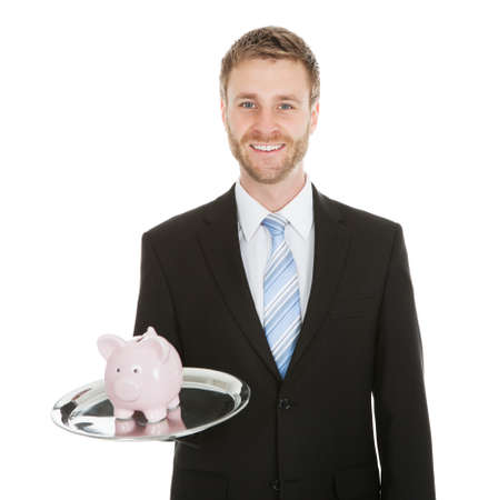 coinbank: Portrait of mid adult businessman with piggybank on tray over white background Stock Photo