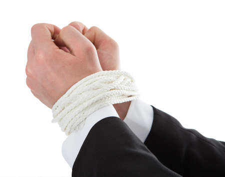 wrongdoing: Closeup of businessmans hands tied with rope over white background