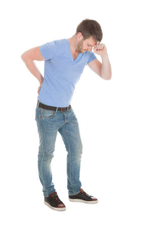 Full length of mid adult man suffering from backache over white background photo