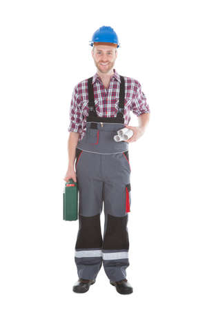 Full length portrait of confident architect holding rolled blueprints and tool kit over white background photo