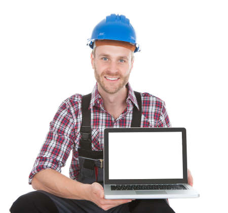 tradesmen: Portrait of young manual worker displaying laptop over white background