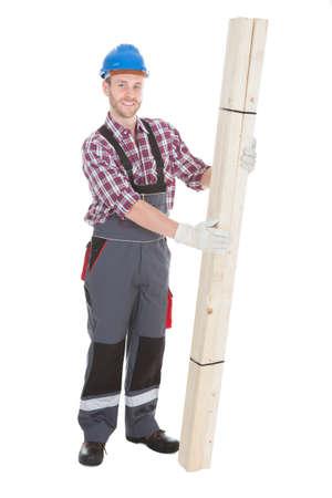 Full length portrait of male carpenter holding wooden planks over white background