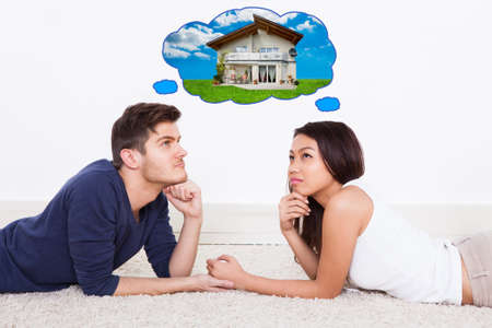 soñando: Vista lateral de la joven pareja pensamiento de casa de sus sueños