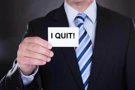 Midsection of businessman showing card with I Quit sign photo