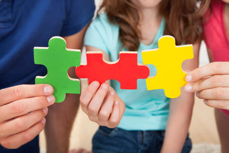 Midsection of family joining puzzle pieces at home photo