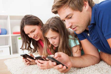 Rodina pomocí chytrých telefonů když ležel na koberci doma Reklamní fotografie