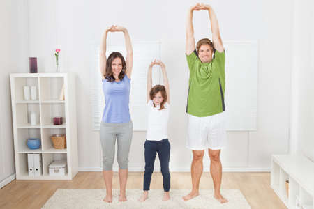 Full length portrait of fit family performing yoga at home photo