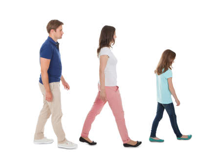Full length side view of family walking in a row isolated over white background