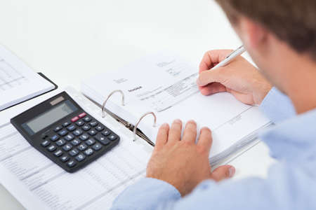tax consultants: Cropped image of businessman calculating tax at desk in office