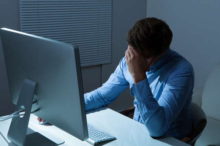 late thirties: Overstressed businessman leaning at computer desk in office
