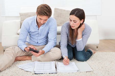 finance: Full length of couple calculating budget in living room at home Stock Photo