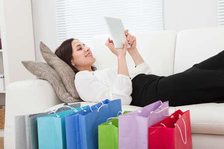 Volledige lengte zijaanzicht van jonge zakenvrouw met behulp van digitale tablet met boodschappentassen op vloer thuis