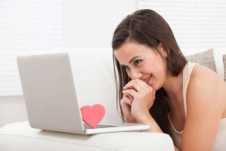 human relationships: Side view of beautiful young woman dating online on laptop at home Stock Photo
