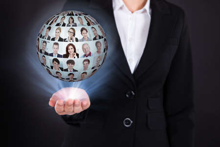Midsection of businesswoman holding businesspeople collage in sphere over black background Stock Photo - 30787003