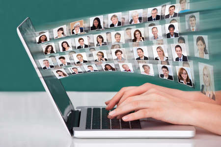 Cropped image of hands using laptop with businesspeople collage