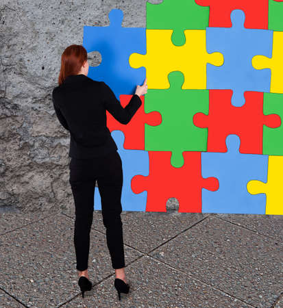 Full length rear view of businesswoman solving colorful jigsaw puzzle against wall photo