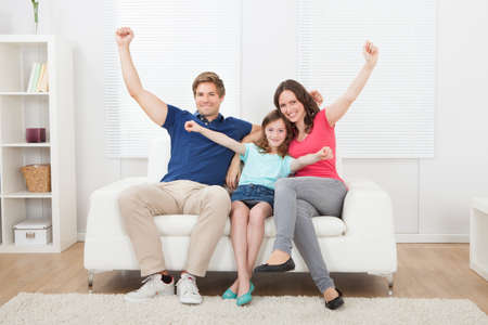 Full length portrait of cheerful family with arms raised sitting on sofa at home photo