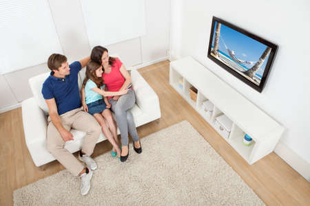 woman sitting on floor: High angle view of family watching TV together while relaxing on sofa at home