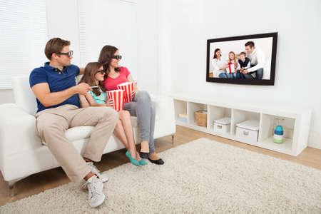 Longitud total de la familia viendo la película en 3D en la televisión, mientras que comer rosetas de maíz en el país
