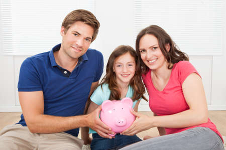 Portrait of happy family holding piggy bank while sitting on floor at home