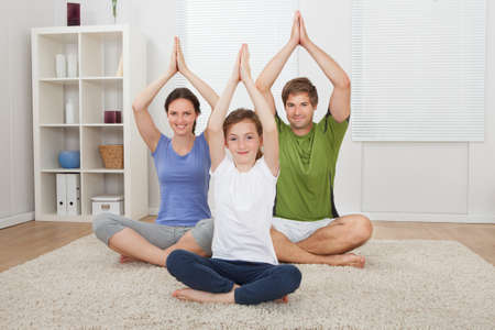 Portrait of smiling family practicing yoga on rug at home photo