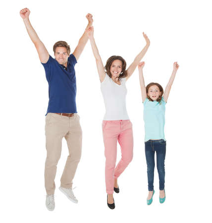 Full length portrait of excited family jumping against white background photo