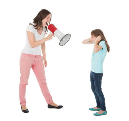 Full length of angry mother shouting through megaphone at daughter against white background