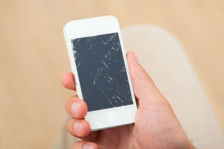cropped image: Cropped image of mans hand holding smartphone with broken screen at home